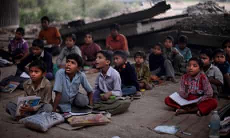 Indian children attend a school run under a bridge in New Delhi, India