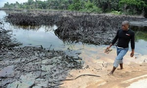 A man walks near the spilled crude oil in Bodo, Niger delta