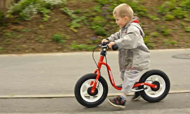 Bike blog : Boy riding a balance bicycle on the sidewalk