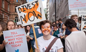 A young demonstrators holds a placard, calling to divest from fossil fuels.
