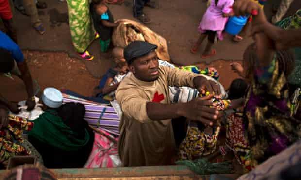 Father Bernard Kenvi helps a Muslim child climb down from an open truck in Bossemptele