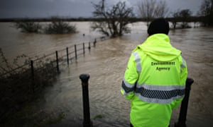Floods defence budget cuts : An Environment Agency employee looks at flood water from the river Arun