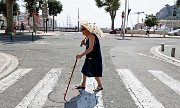 Elderly woman holding an umbrella crosses a street during summer heatwave in Nice, France