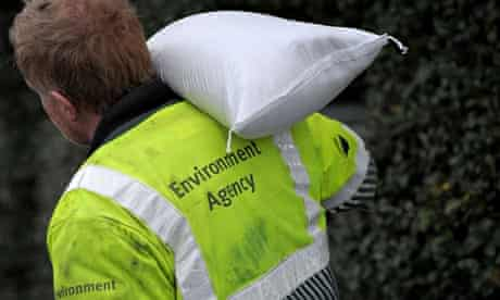 An Environment Agency worker carries a sandbag for floods defences in Sommerset