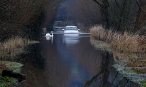 Flooded road on on the Somerset Levels : A car drives through flood water