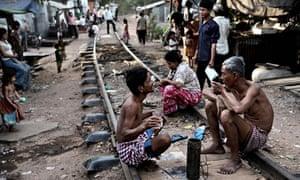 MDG : ADB and Cambodia rail system : People sit along railway, Boeng Kak slum, Phnom Penh