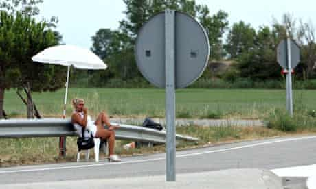 MDG : EU prostitution new law : prostitute sitting on a chair waiting on a road