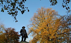 WWI war memorial with soldier statue  in front of autumnal trees near Manchester