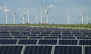 Wind turbines stand behind a solar power park near Werder, Germany.