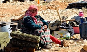 A Syrian woman refugee sits near her belongings
