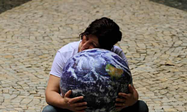 An environmentalist embraces a globe during the Rio+20 UN sustainable development summit in Rio de Janeiro in June, 2012