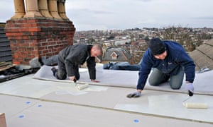 Green Deal : Roofers spreading adhesive over insulation for new EPDM rubber roofing membrane