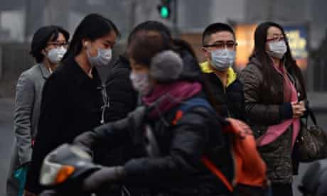 Chinese commuters wear face masks as heavy air pollution continues to shroud Beijing