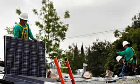 Renewable energy jobs : employees install solar panels on the roof of a home
