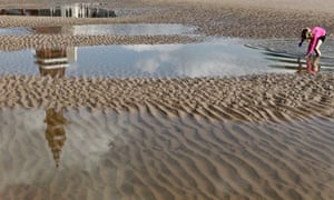Blackpool Tower is reflected in a puddle as a girl plays on Blackpool beach