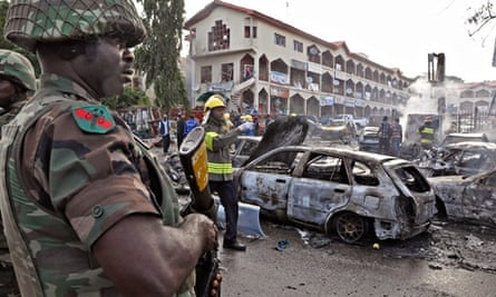 A soldier stands guard at the scene of an explosion in Abuja