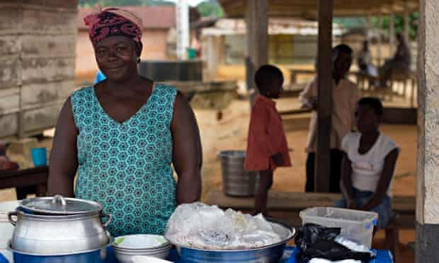 MDG : Smuggling cocao from Ghana to Ivory Coast : A woman sells fish and rice in Adonikrom's market