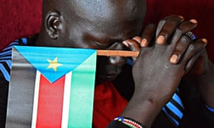 MDG : South Sudan : A man holds a South sudan flag