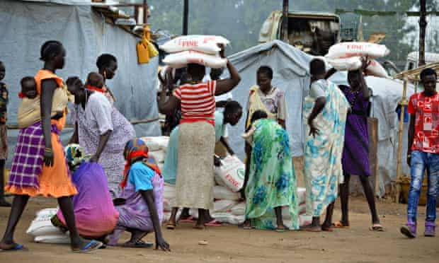 MDG : Food in Africa : Women carry maize flour sacks during a food distribution, Juba, South Sudan