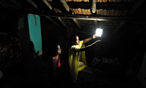 Villagers switches on a light powered by solar energy in the village of Morabandar, India