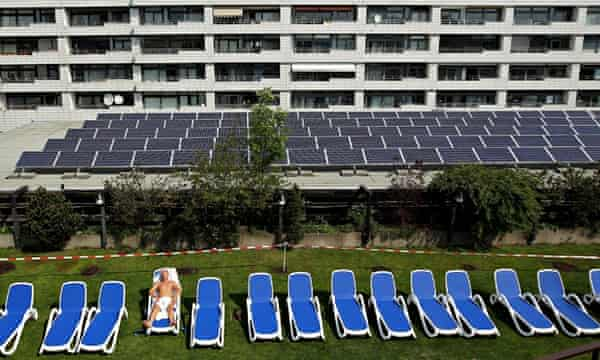Solar energy in Germany : A man sunbathes at a rooftop spa next to solar cell panels in Berlin