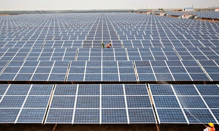 Workers install photovoltaic solar panels at the Gujarat solar park under construction in the western Indian state of Gujarat.