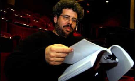 Neil LaBute reads a script in an empty theatre auditorium