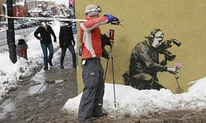 A passerby looks at artwork by Banksy at the Sundance film festival in Park City, Utah