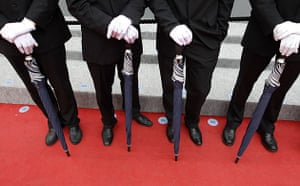 Cannes film festival day8: Cannes film festival officials with umbrellas on the red carpet