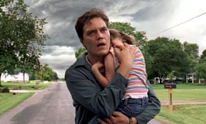 Take Shelter: distressed man carries young daughter as stormclouds mass behind them