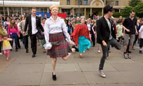 Tilda Swinton leads a flashmob alongside, to her left, Mark Cousins.