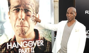 Mike Tyson alongside a Hangover Part II poster featuring Ed Helms and the controversial tattoo.