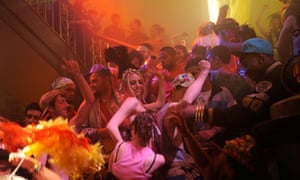 A mass of attractive young ravers dance on a staircase in a still from the film Weekender