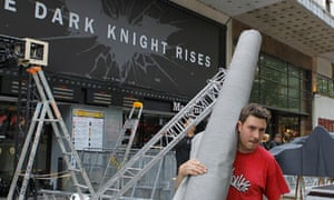 Workers dismantle an installation setup for the premiere of The Dark Knight Rises in Paris.