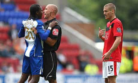 Howard Webb holds back Wigan's Hugo Rodallega from Manchester United's Nemanja Vidic.