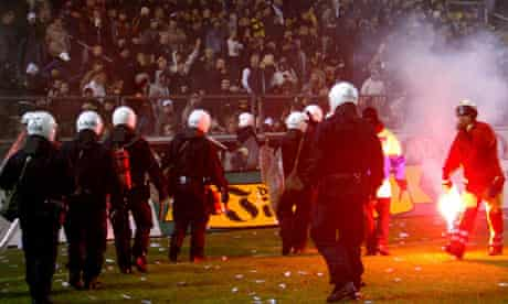 Police try to stop fans going on to the pitch during a match between AIK and Hammarby in 2004