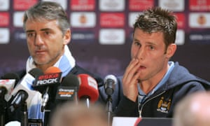 Roberto Mancini, manager of Manchester City, and James Milner face the media in Poznan
