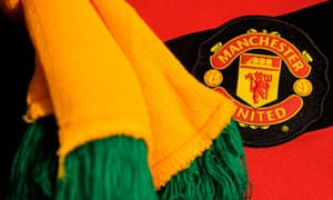 A Manchester United fan wears a green and yellow scarf