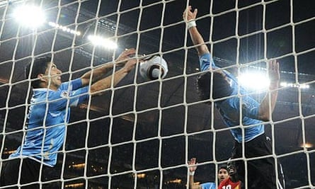 Luis Suárez, left, punches the ball out of the net during Uruguay's win over Ghana on Friday