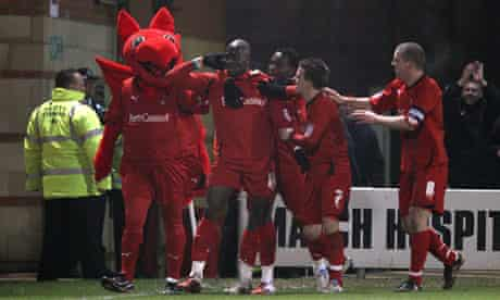 Jonathan Tehoue celebrates with Leyton Orient's mascot after scoring the equaliser against Arsenal