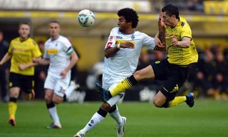 Borussia Moenchengladbach's Dante is challenged by Robert Lewandowski of Dortmund