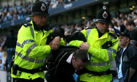 A fan is evicted from Eastlands during a derby encounter