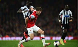 Arsenal's Aaron Ramsey, centre, battles with Cheick Tioté of Newcastle United