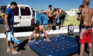 Argentina fans look sheepish as their mate scrubs clean an airbed.