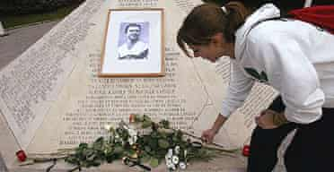 Hungarian athlete Krisztina Komiszar puts a flower at the memorial place for the Hungarian football legend Ferenc Puskas in front of the Puskas Stadium in Budapest