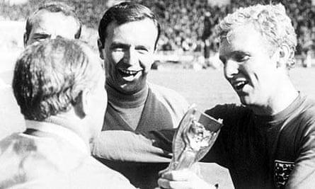 Bobby Moore passes the World Cup trophy to manager Alf Ramsey