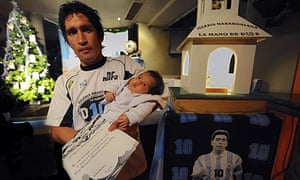 Daniel Astilleta poses with his baby Bianca after she became a member of the Maradonian Church