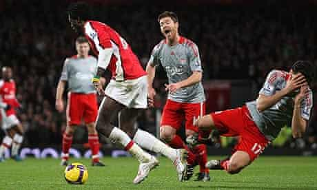 Emmanuel Adebayor of Arsenal tangles with Alvaro Arbeloa of Liverpool