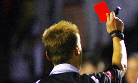 A referee brandishes a red card