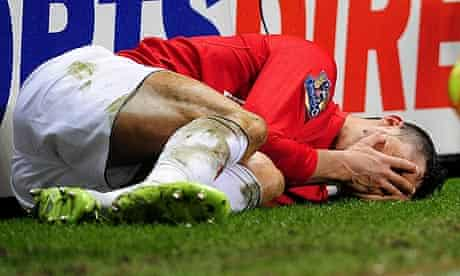 Cristiano Ronaldo holds his face after a tackle on him by Steven Taylor